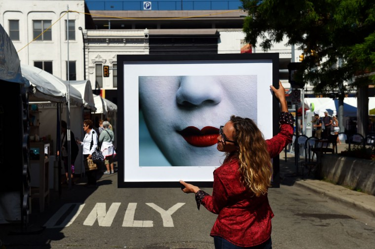 Photographer Lisa Kristine, of San Francisco, Cali., holds one of her photographs in the light to show a customer during the Ann Arbor State Street Art Fair on Wednesday, July 15, 2015 in Ann Arbor, Mich. The fairs are open Wednesday through Friday from 10 a.m. to 9 p.m. and Saturday from 10 a.m. to 6 p.m. (Melanie Maxwell/The Ann Arbor News via AP)