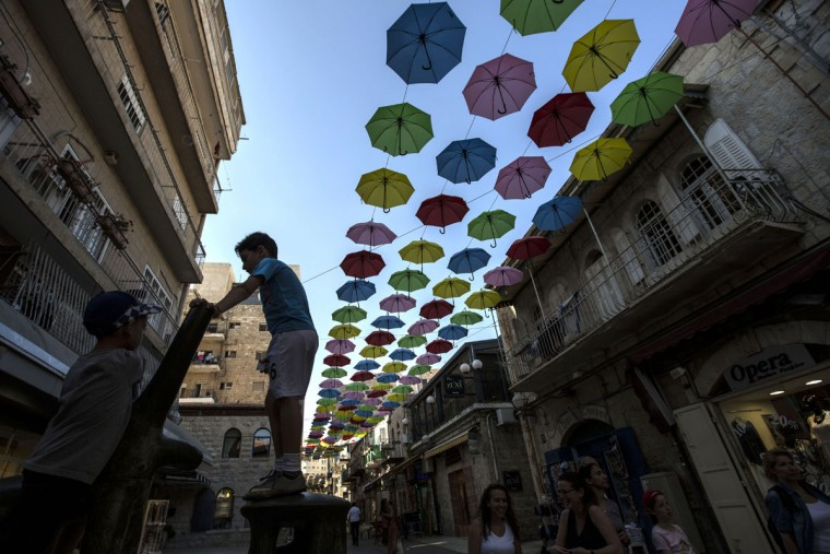 Kids play under colorful umbrellas suspended over a pedestrian street in Jerusalem, Wednesday, July 8, 2015. (AP Photo/Tsafrir Abayov)