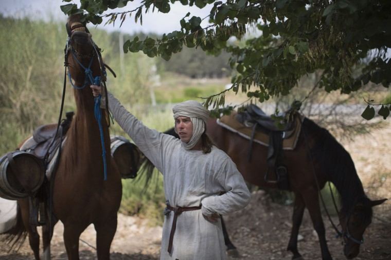 In this Friday, July 3, 2015 photo, Israeli and Russian members of knight clubs get on their horses before marching 27 kilometers (17 miles) to the reenactment of the Battle of Hattin from the ancient northern city of Zippori to Horns of Hattin, northern Israel. Some 60 history buffs are re-enacting the famed battle near an extinct volcano in northern Israel overlooking the Sea of Galilee, where Saladin's army defeated the crusaders at the end of the 12th century. (AP Photo/Oded Balilty)