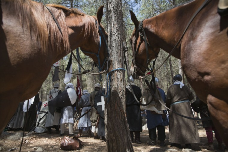 In this Saturday, July 4, 2015 photo, Israeli and Russian members of knight clubs get ready for the reenactment of the Battle of Hattin in Lavi Forest, northern Israel. Some 60 history buffs are re-enacting the famed battle near an extinct volcano in northern Israel overlooking the Sea of Galilee, where Saladin's army defeated the crusaders at the end of the 12th century. (AP Photo/Oded Balilty)