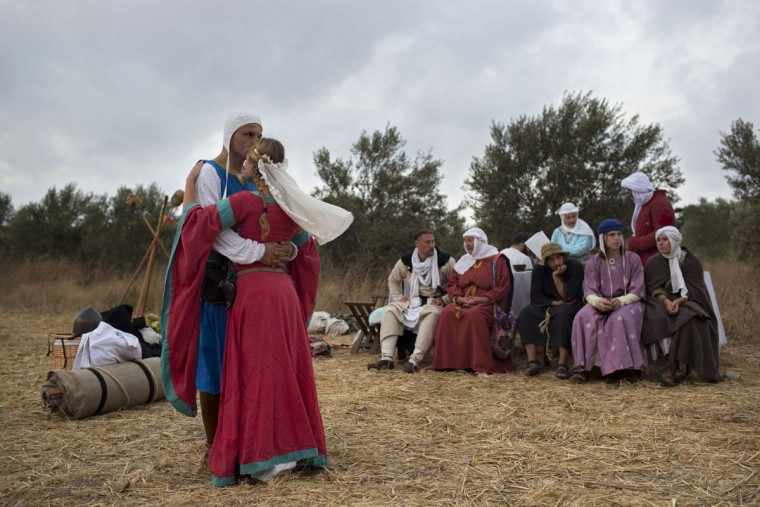 In this Thursday, July 2, 2015 photo, Israeli and Russian members of knight clubs wearing medieval costumes arrive to their camp before marching 27 kilometers (17 miles) to the reenactment of the Battle of Hattin from the ancient northern Israeli city of Zippori to Horns of Hattin, northern Israel. Some 60 history buffs are re-enacting the famed battle near an extinct volcano in northern Israel overlooking the Sea of Galilee, where Saladin's army defeated the crusaders at the end of the 12th century. (AP Photo/Oded Balilty)