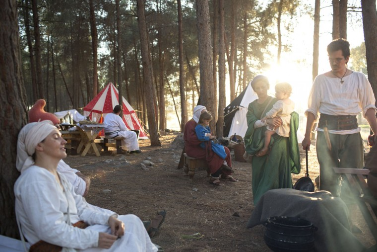 In this Friday, July 3, 2015 photo, Israeli and Russian members of knight clubs cook their dinner before the reenactment of the Battle of Hattin in Lavi Forest, northern Israel. About a third of the participants arrived with their elaborate gear from Russia. The project is supported by the Lower Galilee Regional Council. (AP Photo/Oded Balilty)