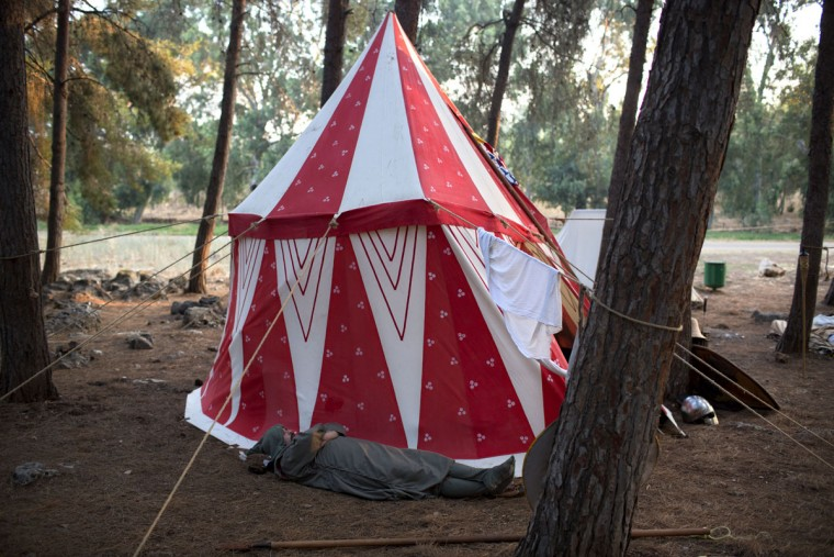 In this Friday, July 3, 2015 photo, an Israeli member of a knight club wearing a medieval costume rests in their camp before the reenactment of the Battle of Hattin in Lavi Forest, northern Israel. Some 60 history buffs are re-enacting the famed battle near an extinct volcano in northern Israel overlooking the Sea of Galilee, where Saladin's army defeated the crusaders at the end of the 12th century. (AP Photo/Oded Balilty)