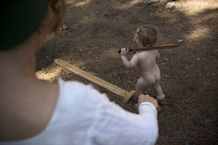 In this Saturday, July 4, 2015 photo, an Israeli boy plays with his mother, a member of a knight club, before the reenactment of the Battle of Hattin in Lavi Forest, northern Israel. Some 60 history buffs are re-enacting the famed battle near an extinct volcano in northern Israel overlooking the Sea of Galilee, where Saladin's army defeated the crusaders at the end of the 12th century. (AP Photo/Oded Balilty)