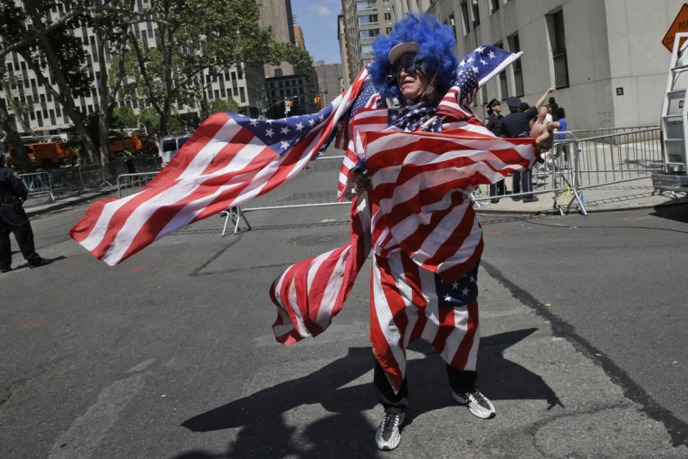 A U.S. women's soccer team fan is covered in American flags during the ticker-tape parade to celebrate their World Cup victory, Friday, July 10, 2015, in New York. (AP Photo/Mary Altaffer)