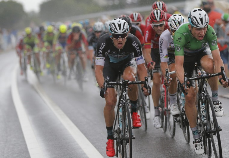 The pack with Germany's Tony Martin, wearing the best sprinter's green jersey, rides in the rain during the second stage of the Tour de France cycling race over 166 kilometers (103 miles) with start in Utrecht and finish in Neeltje Jans, Netherlands, Sunday, July 5, 2015. (AP Photo/Christophe Ena)