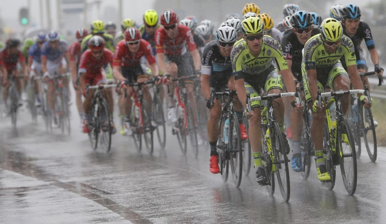 The pack rides in the rain during the second stage of the Tour de France cycling race over 166 kilometers (103 miles) with start in Utrecht and finish in Neeltje Jans, Netherlands, Sunday, July 5, 2015. (AP Photo/Christophe Ena)