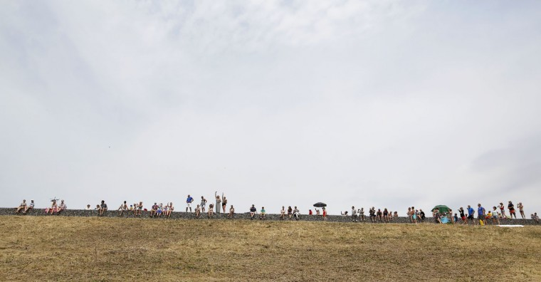 People line a dyke as the watch the pack pass by during the second stage of the Tour de France cycling race over 166 kilometers (103 miles) with start in Utrecht and finish in Neeltje Jans, Netherlands, Sunday, July 5, 2015. (AP Photo/Laurent Cipriani)