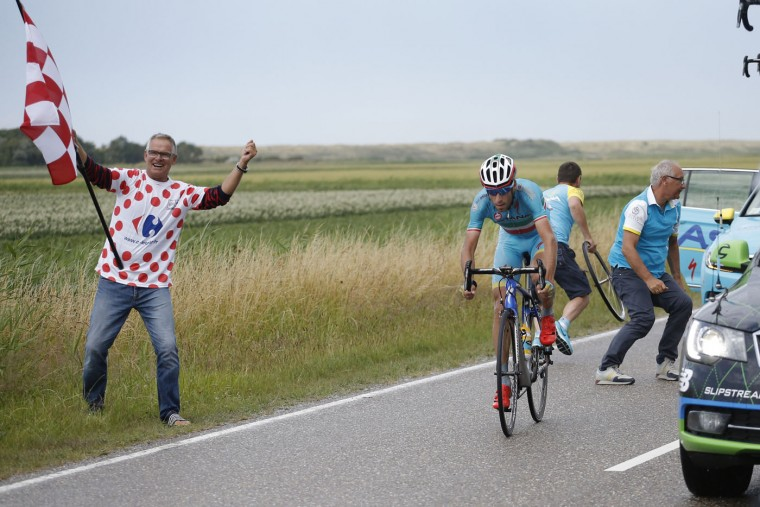 A spectator cheers as Italy's Vincenzo Nibali gets back on his bicycle after changing his tyre following a puncture during the second stage of the Tour de France cycling race over 166 kilometers (103 miles) with start in Utrecht and finish in Neeltje Jans, Netherlands, Sunday, July 5, 2015. (AP Photo/Laurent Cipriani)