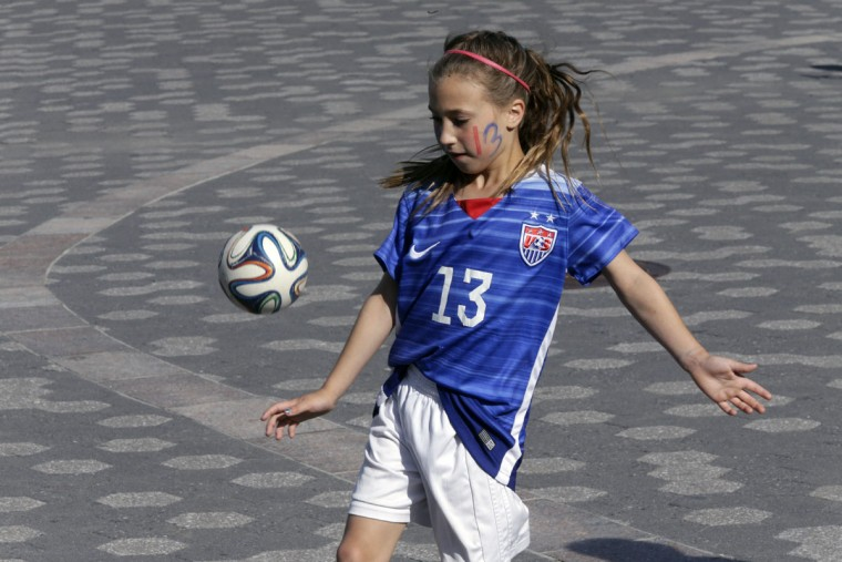 Caigan Leonard, 9, of New Windsor, N.Y., wears a number 13 soccer jersey like team USA player Alex Morgan while waiting for the ticker tape parade to celebrate the U.S. women's soccer team World Cup victory, Friday, July 10, 2015, in New York. (AP Photo/Mary Altaffer)