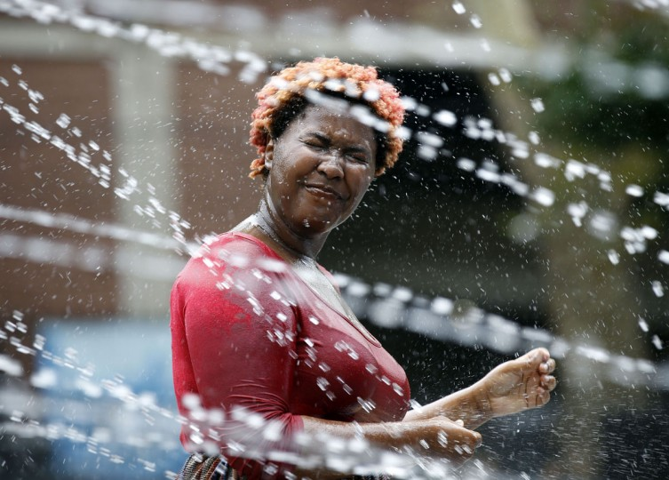 Baseerah Watson, of West Philadelphia, cools off near a water fountain at Seger Park in Philadelphia on Wednesday, July 29, 2015. (Yong Kim/The Philadelphia Inquirer via AP)