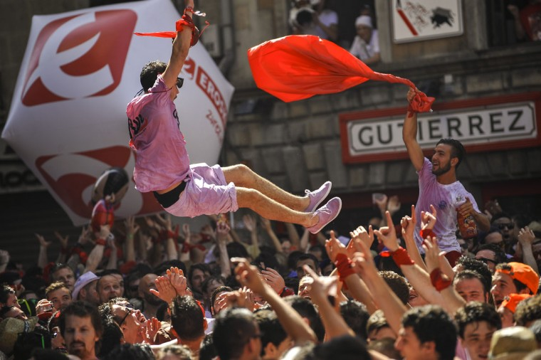 Revelers celebrate during the launch of the 'Chupinazo' rocket, to celebrate the official opening of the 2015 San Fermin Fiestas, in Pamplona, northern Spain, Monday, July 6, 2015. (AP Photo/Alvaro Barrientos)
