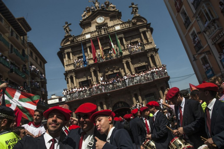 Members of the Gaiteros musician group gesture in front of the City hall, back, while celebrating during the launch of the 'Chupinazo' rocket, to celebrate the official opening of the 2015 San Fermin Fiestas, in Pamplona, northern Spain, Monday, July 6, 2015. (AP Photo/Alvaro Barrientos)