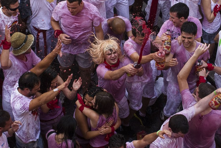 "Revelers throw wine during the launch of the ""Chupinazo"" rocket, to celebrate the official opening of the 2015 San Fermin festival in Pamplona, Spain, Monday, July 6, 2015. (AP Photo/Andres Kudacki)"
