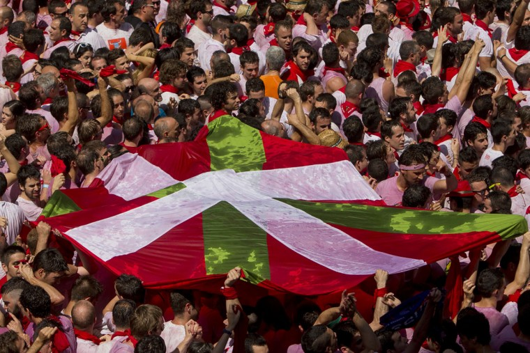 "Revelers hold the basque flag during the launch of the ""Chupinazo"" rocket, to celebrate the official opening of the 2015 San Fermin fiestas in Pamplona, Spain, Monday, July 6, 2015. (AP Photo/Andres Kudacki)"