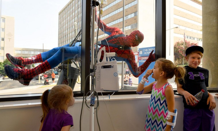 Emma Hatcher, middle, stands near her cousin Eric Fox, right, as Spider-Man window washer Luke Daven entertains the group at East Tennessee Children's Hospital, Monday, July 20, 2015, in Knoxville, Tenn. Spider-Man and fellow super heroes Thor, Captain American and Catwoman washed windows for Sky Clean Inc., of Asheville, N.C. (Michael Patrick/Knoxville News Sentinel via AP)