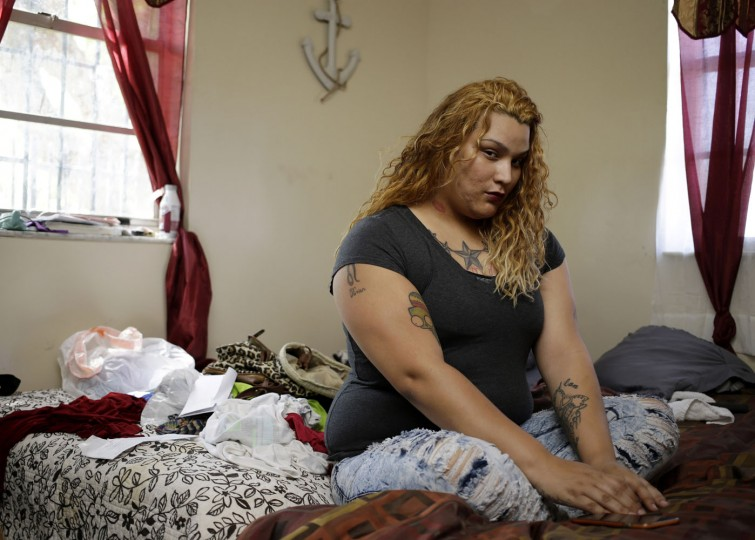 In this photo taken May 1, 2015, Kassidy Suarez, 22, who identifies as a transgender female, poses for a photo in her bedroom in an apartment she shares with her mother in Miami. After coming out at 15, first as a gay young man, and then at age 17 as a transgender woman, Kassidy dropped out of high school, met rejection by her family and ended up homeless. She spent several years on the streets, dabbled with drugs and engaged in survival sex work. With the help of Project SAFE, Suarez found housing, counseling and a support network. She is now focused on getting her GED. (AP Photo/Lynne Sladky)