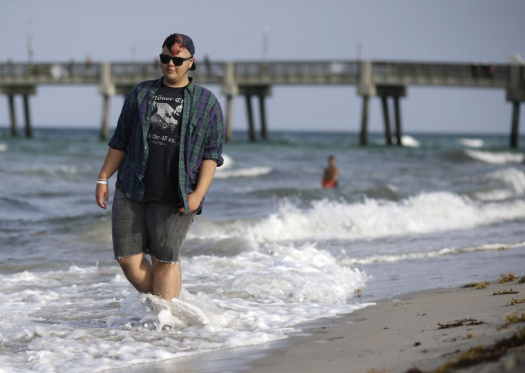 "In this photo taken June 11, 2015, Eli, 17, of Fort Lauderdale, Fla., poses for a photograph walking along the beach in Dania Beach, Fla. Eli has found growing up to be a painful struggle, one that's been at odds to define his gender identity. Born a girl, he has struggled with depression: ""I would look in the mirror and just hate my chest. And just try to squish it down. And just like sob for hours, like I was a little kid."" (AP Photo/Lynne Sladky)"