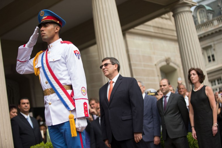 A member of a Cuban honor guard salutes as Cuban Foreign Minister Bruno Rodriguez, center, prepares to raise the Cuban flag over their new embassy in Washington, Monday, July 20, 2015. Cuba's blue, red and white-starred flag was hoisted Monday at the country's embassy in Washington in a symbolic move signaling the start of a new post-Cold War era in U.S.-Cuba relations. (AP Photo/Andrew Harnik, Pool)