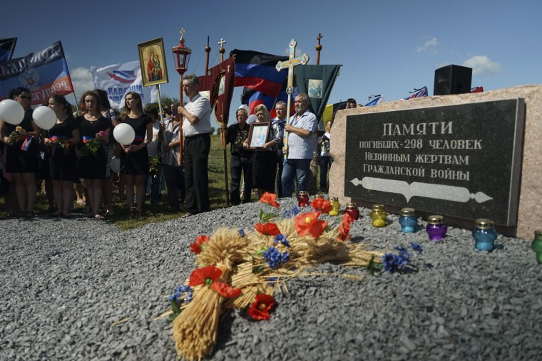 People stand with Orthodox crosses and icons as they attend a memorial service at the crash site of the Malaysia Airlines Flight 17, near the village of Hrabove, eastern Ukraine, Friday, July 17, 2015. In a solemn procession, residents of the Ukrainian village where a Malaysian airliner was shot down with 298 people aboard a year ago marched Friday to the crash site. (AP Photo/Mstyslav Chernov)
