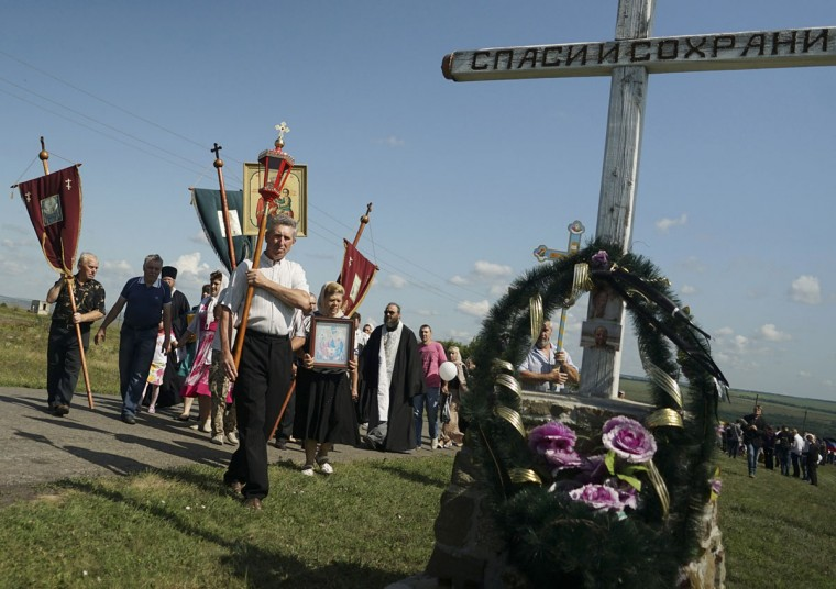 A religious procession passes an Orthodox cross with a sign reading Save and Guard at the crash site of the Malaysia Airlines Flight 17, near the village of Hrabove, eastern Ukraine, Friday, July 17, 2015. Residents of the Ukrainian village where the Malaysian airliner was shot down with 298 people aboard a year ago began a procession to the crash site on Friday, while the Australian prime minister remembered the ìsavageryî of the disaster by unveiling a plaque in Canberra thatís set in soil from the place where the plane went down. (AP Photo/Mstyslav Chernov)