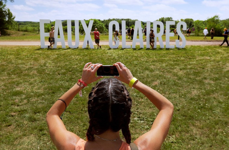 Festival-goers take turns having their photo taken next to the EAUX CLAIRES sign Friday, July 17, 2015, along the Chippewa River on the grounds of the Eaux Claires Music & Arts Festival in Eau Claire, Wis. (AP Photo/Eau Claire Leader-Telegram, Marisa Wojcik)