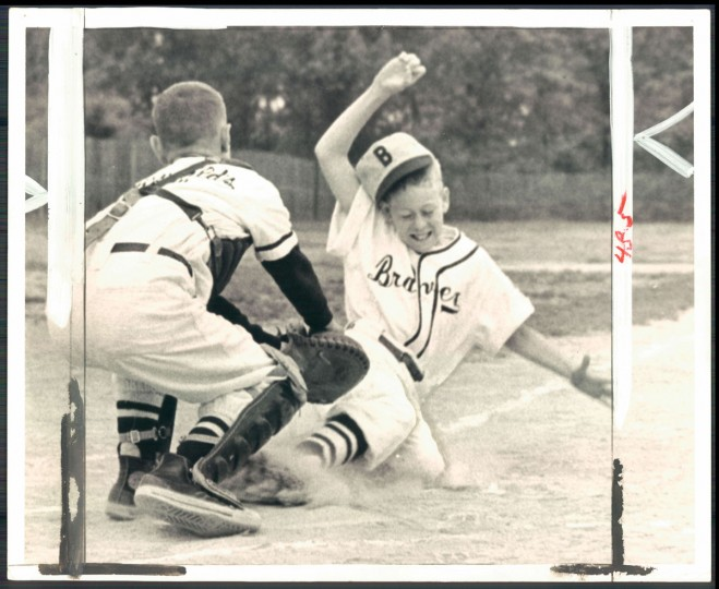 Charles Lannak of Hauswalds Bakery Orioles, catcher, making out on Anderson Chevrolet Brave centerfielder Gary Michael. (Ralph Robinson/Baltimore Sun, 1962)