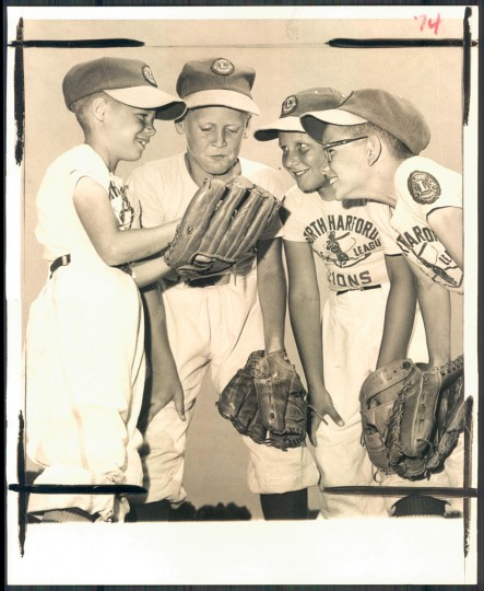 Diminutive shortstop Mike Brennan fondles a baseball in his large glove as the other infielders on the Parkville Lion team gaze in admiration of the defensive standout. Lions Fred Traut, Mike Wajda and Wayne Davis are Brennan's admirers. (Clarence B. Garrett/Baltimore Sun, 1964)