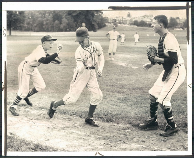 Third-baseman Mark Sweitzer and catcher Mike Curran work on trap play with runner Mike Guewa as the American all-stars prepare for the Sept. 1 all-star cub game. (Joseph DiPaola/Baltimore Sun, 1962)