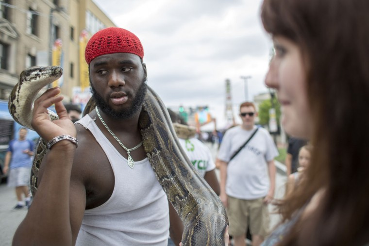 "Aaron Hemsley holds his pet snake, ""Big Momma"" on Charles Street at Artscape. (Tom Brenner / The Baltimore Sun)"