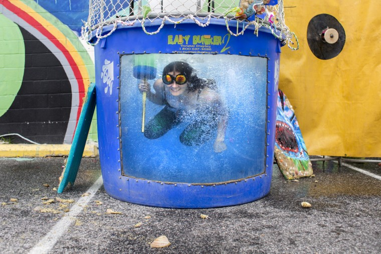 Jessie Delaplaine looks through a dunk tank at the Baltimore Rock Opera Exhibit at Artscape. (Tom Brenner / The Baltimore Sun)
