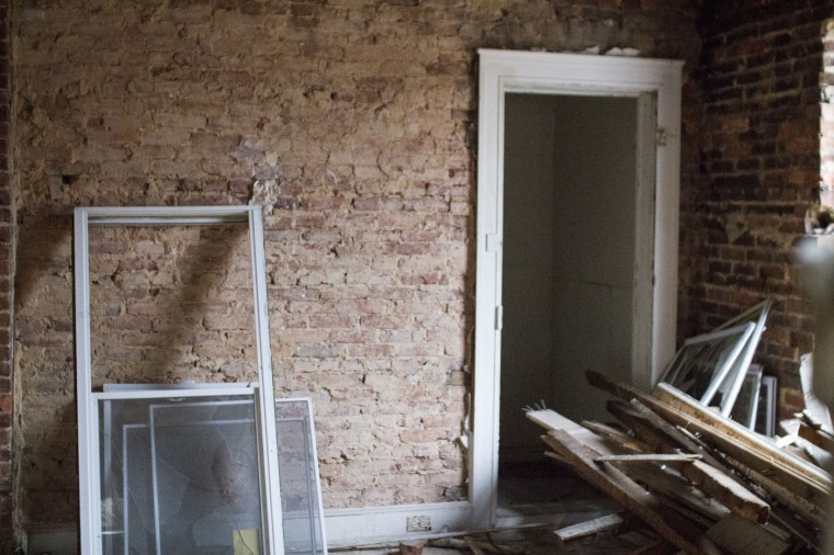 A vacant home in the 900 block of N. Port Street had once attempted to be rehabbed - new windows were half-installed in the home at the time Details was deconstructing the block. (Kalani Gordon, Baltimore Sun)