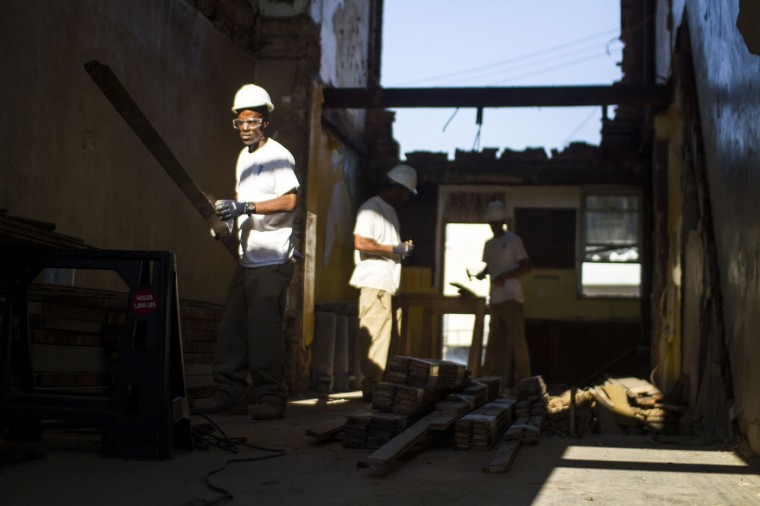 A Details employee pulls nails and sands down boards from one of the vacant homes in the 900 block of N. Port Street. (Kalani Gordon, Baltimore Sun)