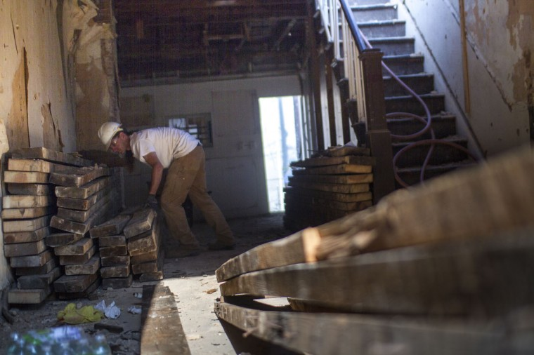 A Details employee stacks boards from a vacant home in the 900 block of N. Port Street. (Kalani Gordon, Baltimore Sun)