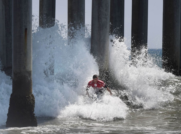 Professional surfer Tim Reyes of the US 'Shoots the Pier' during his round two men's heat of the US Open of Surfing in Huntington Beach, California on July 29, 2015. The event celebrates it's 56th year beside the historic Huntington Pier which is considered the birthplace of California's surfing culture. (Mark Ralston/Getty Images)
