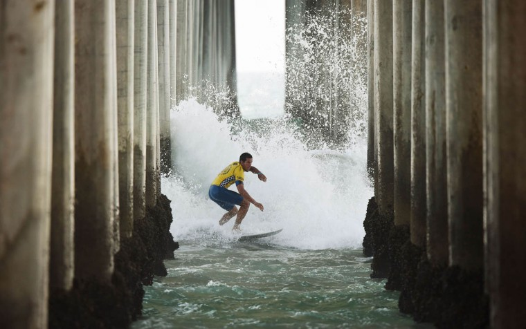 Professional surfer Ian Gouveia of Brazil 'Shoots the Pier' during his round two men's heat of the US Open of Surfing in Huntington Beach, California on July 29, 2015. The event celebrates it's 56th year beside the historic Huntington Pier which is considered the birthplace of California's surfing culture. (Mark Ralston/Getty Images)