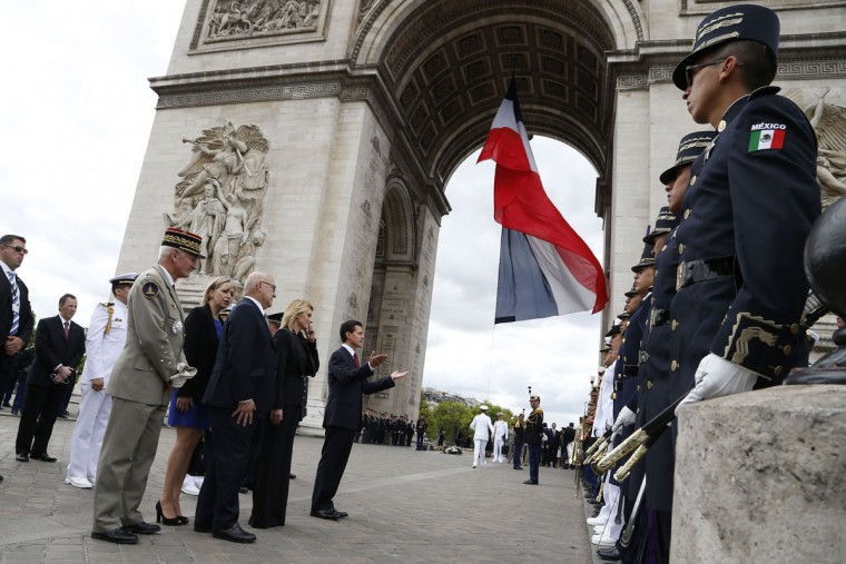 French General Herve Charpentier, Paris' Military Governor (left) stands along side French Economy, Finance Trade Minister Michel Sapin, Mexican First Lady Angelica Rivera and Mexican President Enrique Pena Nieto, as they attend a wreath laying ceremony on the tomb of the unknown soldier at the Arc de Triomphe monument in Paris, on Bastille Day, on July 14, 2015. (THOMAS SAMSON/AFP/Getty Images)