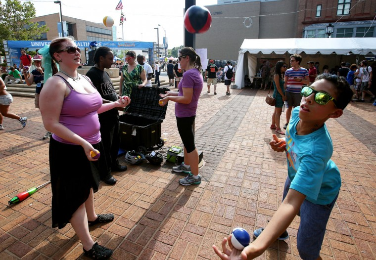 Left: Heidi Thalman teaches Right:12-year-old Braden Morrison how to juggle during Artscape in Baltimore, Maryland. (Daniel Kucin Jr./Baltimore Sun)