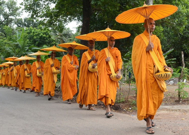 Sri Lankan Buddhist monks walk in line as they seek offerings of food in Colombo on July 25, 2015. The Buddhist majority nation later in the month will commemorate the introduction of Buddhism to the island, which spread with the arrival of Emperor Ashoka from neighboring India during the 3rd century. (Lakruwan Wanniarachichi/AFP-Getty Images)