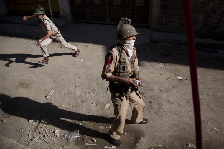 Indian police men take cover from stones and rocks thrown at them by Kashmiri Muslim protesters during a protest amid a strike in Srinagar, Indian controlled Kashmir, Saturday, July 25, 2015. Shops, businesses and schools are shut in Indian-controlled Kashmir after a strike called by traders' organization and separatist groups against alleged burning of a flag bearing Islamic verses in Rajouri district, according to local news reports. (Associated Press/Dar Yasin)