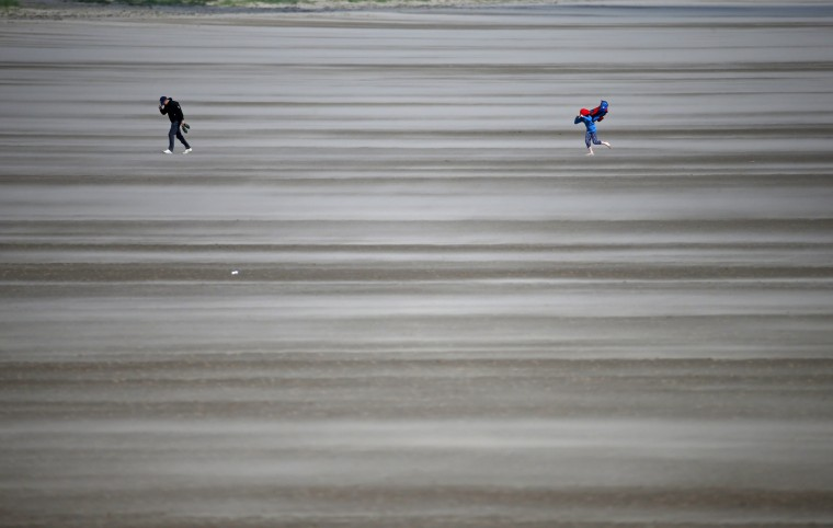 People walk on a windswept beach near the course as high winds suspend play during the second round of the British Open Golf Championship at the Old Course, St. Andrews, Scotland, Saturday, July 18, 2015. (Jon Super/Associated Press)