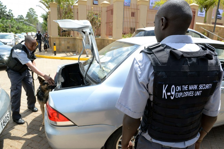 Employees of a private security company with a sniffer dog inspect cars outside the Westgate shopping mall after it reopened on July 18, 2015 in Nairobi. Kenya's Westgate shopping mall reopened for business on July 18, almost two years after Somali Islamists stormed in and massacred 67 shoppers and staff in four days of carnage. (Simon Maina/AFP-Getty Images)
