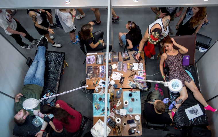 Tattoo artists work as visitors walk by, during the Moscow International Tattoo Week in Moscow on July 25, 2015. (Alexander Utkin/AFP-Getty Images)