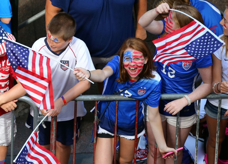 A young fan cheers while waiting for the ticker tape parade to celebrate the U.S. women's soccer team World Cup victory, Friday, July 10, 2015, in New York. (AP Photo/Adam Hunger)