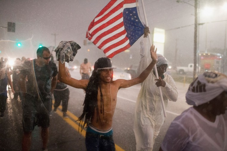 Demonstrators, marking the one-year anniversary of the shooting of Michael Brown, march along West Florrisant Street in a driving rain on August 9, 2015 in Ferguson, Missouri. There are reports that two people were shot when gun fire broke out during protests later in the evening. Brown was shot and killed by a Ferguson police officer on August 9, 2014. His death sparked months of sometimes violent protests in Ferguson and drew nationwide focus on police treatment of black offenders. (Photo by Scott Olson/Getty Images)