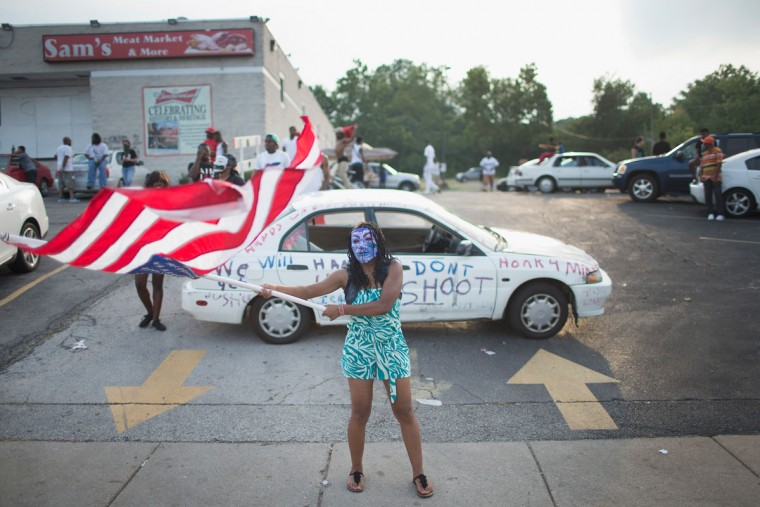Demonstrators, marking the one-year anniversary of the shooting of Michael Brown, protest along West Florrisant Street on August 9, 2015 in Ferguson, Missouri. There are reports that two people were shot when gun fire broke out during protests later in the evening. Brown was shot and killed by a Ferguson police officer on August 9, 2014. His death sparked months of sometimes violent protests in Ferguson and drew nationwide focus on police treatment of black offenders. (Photo by Scott Olson/Getty Images)