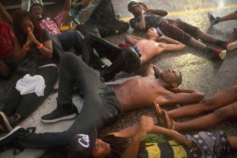 Demonstrators, marking the one-year anniversary of the shooting of Michael Brown, stage a die in along West Florrisant Street in a driving rain on August 9, 2015 in Ferguson, Missouri. There are reports that two people were shot when gun fire broke out during protests later in the evening. Brown was shot and killed by a Ferguson police officer on August 9, 2014. His death sparked months of sometimes violent protests in Ferguson and drew nationwide focus on police treatment of black offenders. (Photo by Scott Olson/Getty Images)