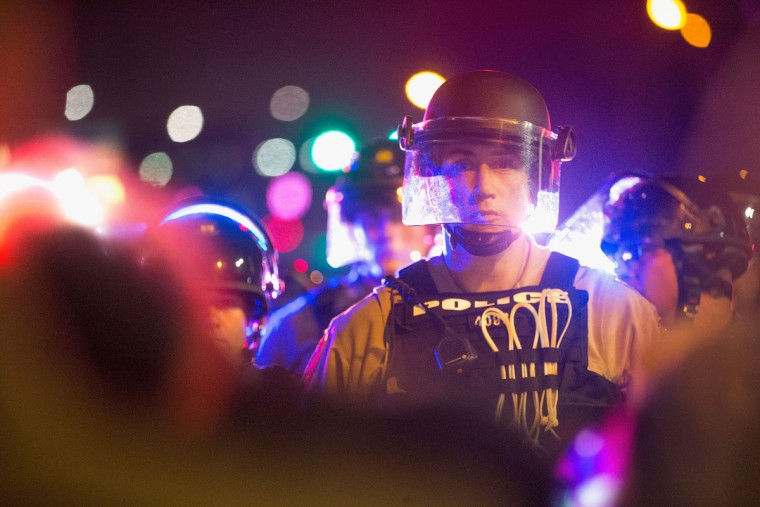 Demonstrators, marking the one-year anniversary of the shooting of Michael Brown, face off with police during a protest along West Florrisant Street on August 9, 2015 in Ferguson, Missouri. There are reports that two people were shot when gun fire broke out during protests later in the evening. Brown was shot and killed by a Ferguson police officer on August 9, 2014. His death sparked months of sometimes violent protests in Ferguson and drew nationwide focus on police treatment of black offenders. (Photo by Scott Olson/Getty Images)