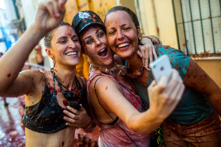 Revelers take a selfie as they enjoy the atmosphere in tomato pulp while participating the annual Tomatina festival on August 26, 2015 in Bunol, Spain. An estimated 22,000 people threw 150 tons of ripe tomatoes in the world's biggest tomato fight held annually in this Spanish Mediterranean town. (Photo by David Ramos/Getty Images)