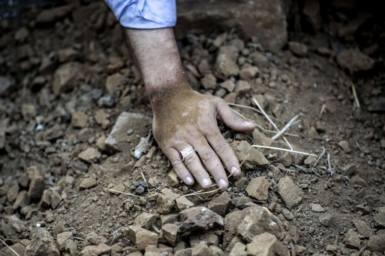 A mourner touches the grave of Vatan Budak, a victim of the suicide bomb attack in Suruc on July 22, during his funeral on August 4, 2015 in Istanbul. Budak died on Monday following his injuries. Turkey vowed on August 3 to pursue its battle against Kurdish militants, who have borne the brunt of almost two weeks of airstrikes while also committing attacks against Turkish forces. (AFP Photo/Ozan Kose)